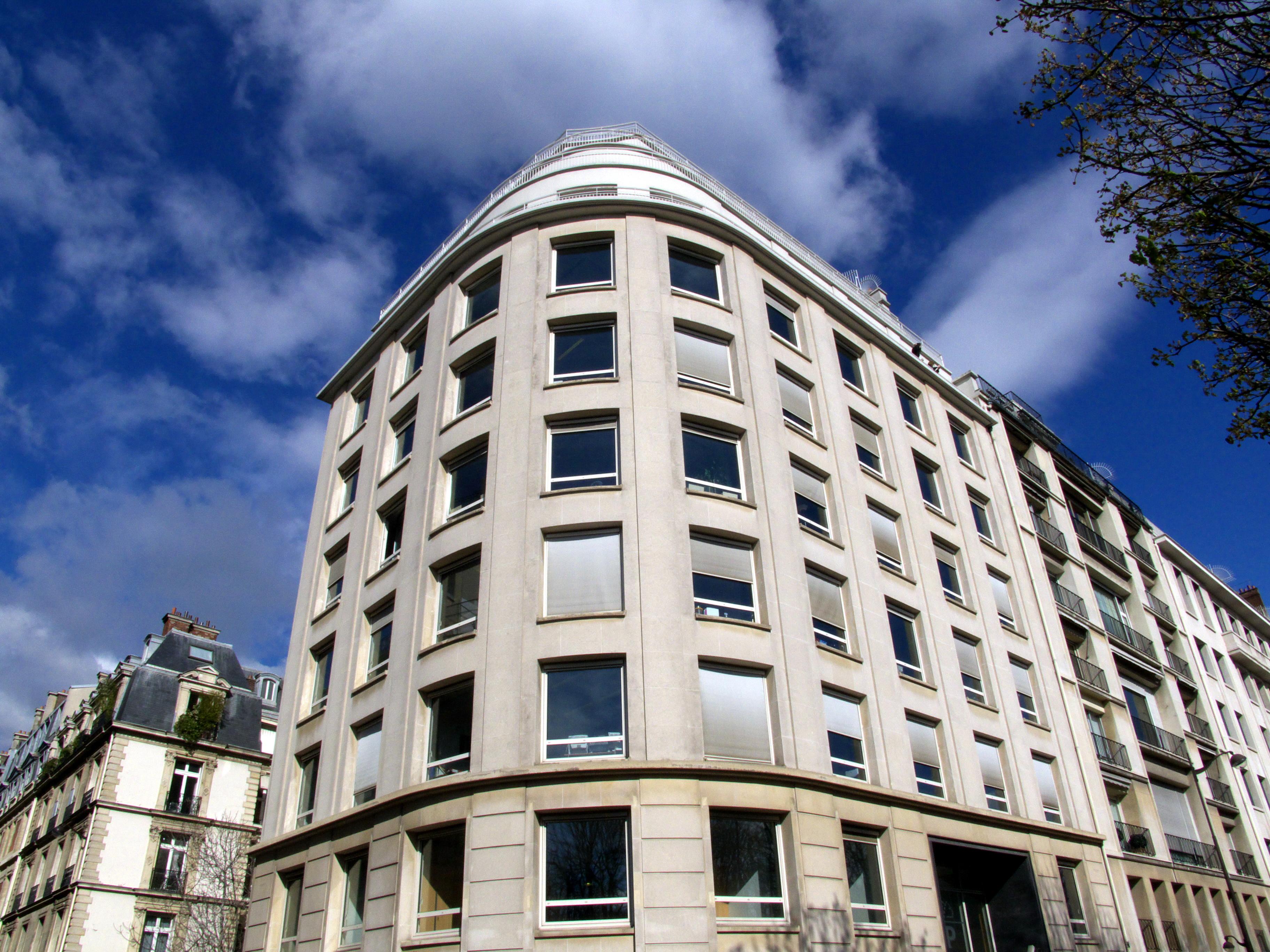 Coin de rue, immeuble blanc arrondi, Paris.