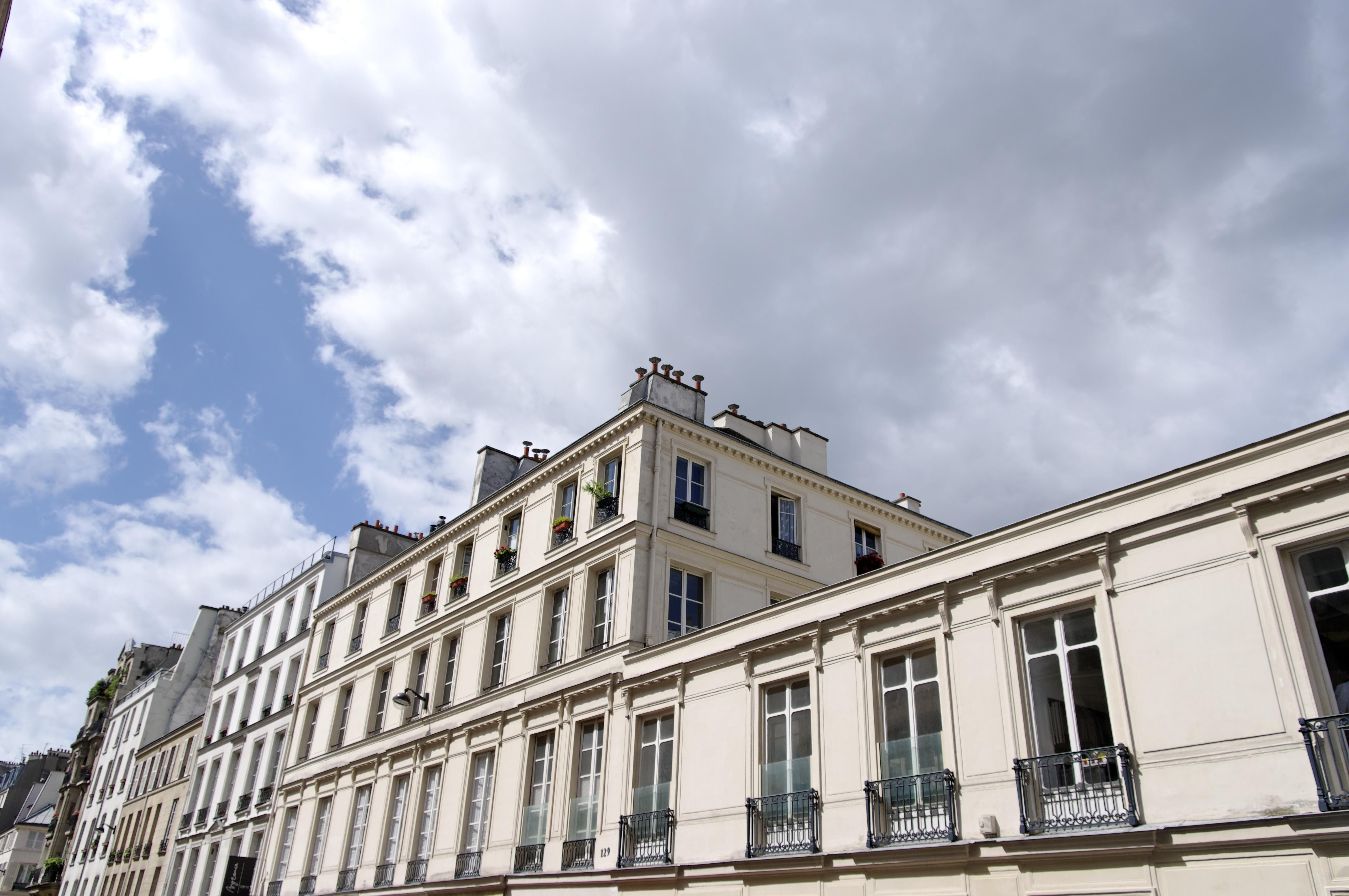 Immeuble dans une rue de Paris, ciel nuageux.